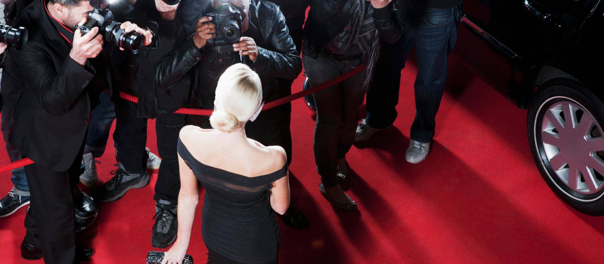 Amazing stories: cameramen taking pictures of a woman on the red carpet