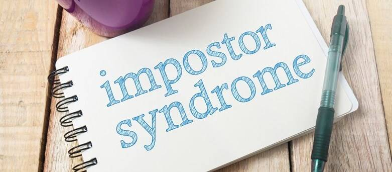 "Blue Arrow Blog - Imposter Syndrome, Notepad on Table with words ""Imposter Syndrome"""