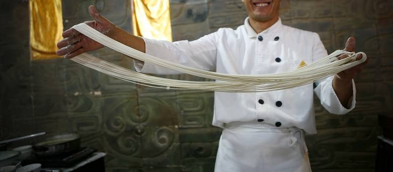 Food and drink events 2020 - male chef demonstrating how dough is stretched.