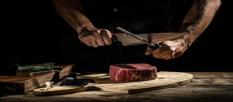 Male sharpening a knife before cutting a piece of steak