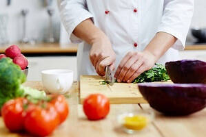 Top 5 Hospitality and Catering Industry trends in 2020 - chef chopping vegetables in the kitchen
