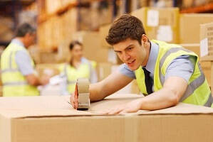 A warehouse worker in the warehouse sealing up a box