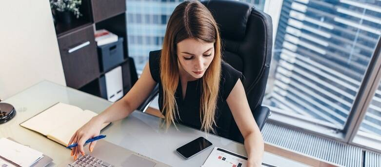 Image of an office worker at her desk with a laptop and paperwork.