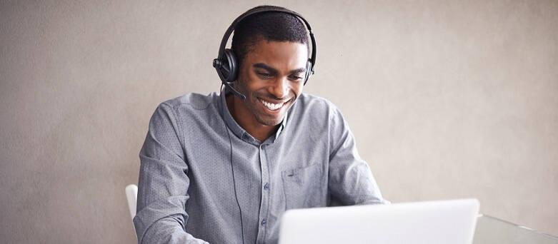 A Customer Services Representative working at home with a laptop and headset