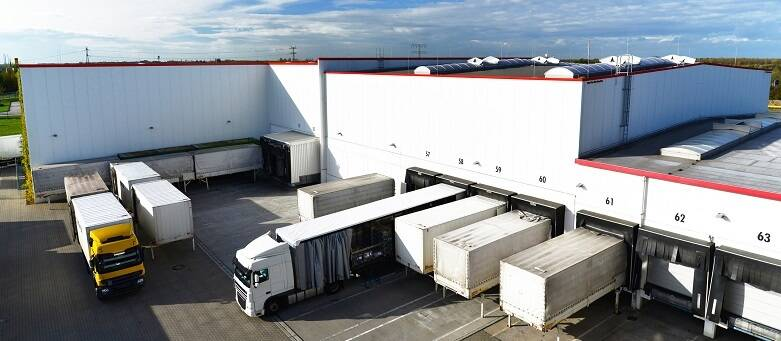 6 ways to be prepared for your next big warehouse career move picture of a warehouse with trucks parked in bays