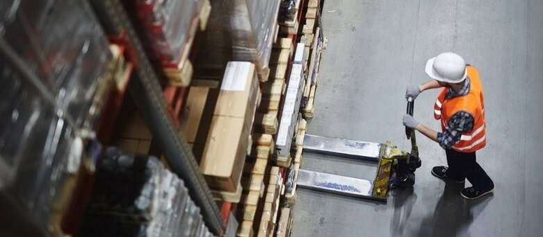 Blue Arrow Warehouse Blog,  7 Important Lessons a Warehouse Workers taught us - Ariel shot of a warehouse worker using a lifting aid to move boxes onto a shelf in a warehouse