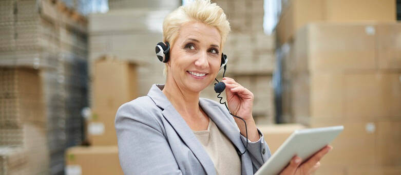 A female worker in a Warehouse environment on the phone via a headset and using a tablet