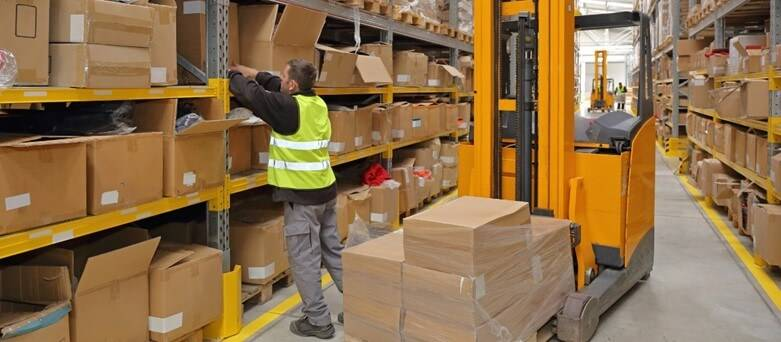 Making the most of your temp warehouse job;male warehouse operative stacking the shelves in a warehouse. A forklift truck is behind him with a pallet of boxes