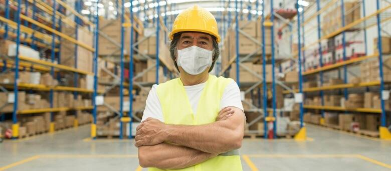 A warehouse worker in the warehouse wearing a mask.