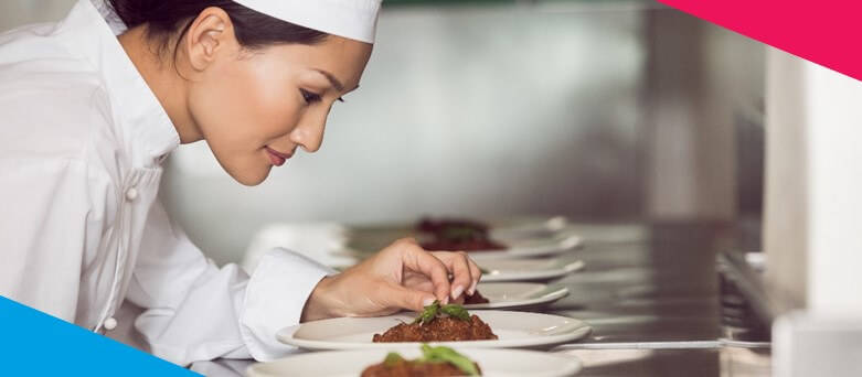 Female Commis Chef putting final touches on dishes