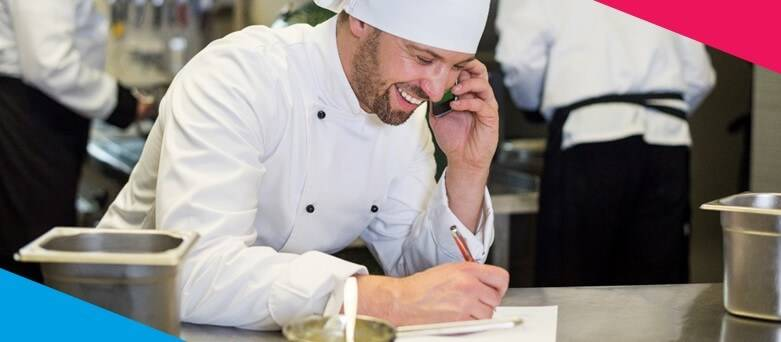 Male Head Chef on the phone and writing