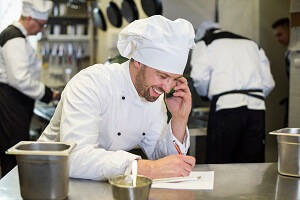 Male Head Chef on the phone ordering ingredients