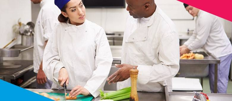 How to become a Kitchen Assistant - a female chef chopping vegetables, a male chef talking teaching the female chef
