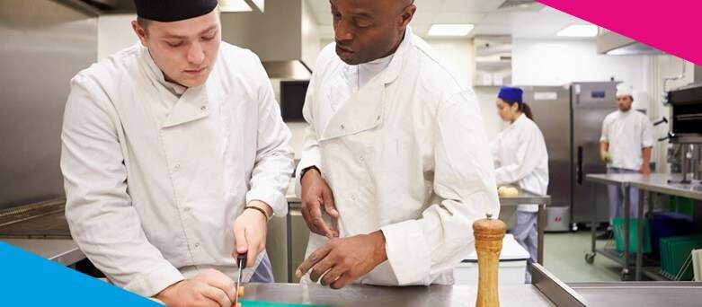 Male catering assistant being trained by chef on chopping up vegetables