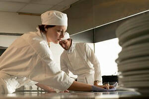 Female and Male Food Service Assistant cleaning a surface in commercial kitchen.
