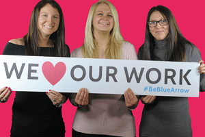 Our People - three consultants holding a board saying we love our work #BeBlueArrow
