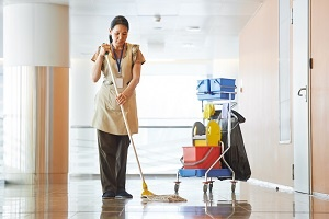 Cleaner mopping the floor of a large hallway