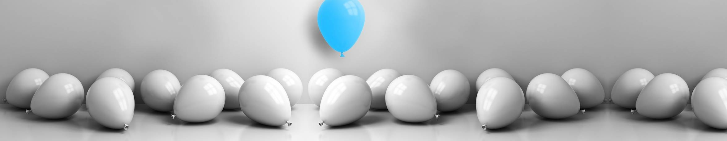 Opinion Article Hero Image, grey balloons scattered on the floor with one blue balloon floating