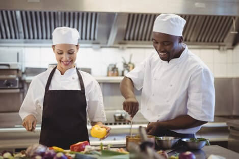 Apprenticeships by Blue Arrow - Chef de Partie: Male and Female Chef chopping vegetables and stirring a pot. How to become a Chef de Partie