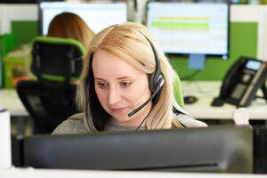 Customer Service Advisor Skills Overview  - Female Customer Service Advisor with headset speaking on the phone and using computuer.