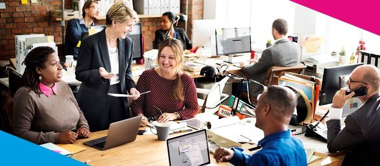 Picture of an office environment, depicting an Account Manager in discussion with a colleague