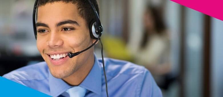 Lloyds Banking Group, Customer Analyst  Job Description, Male in an office setting with a headset speaking on the phone