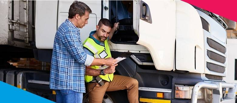 Driver at the side of the vehicle discussing delivery checklist with another person