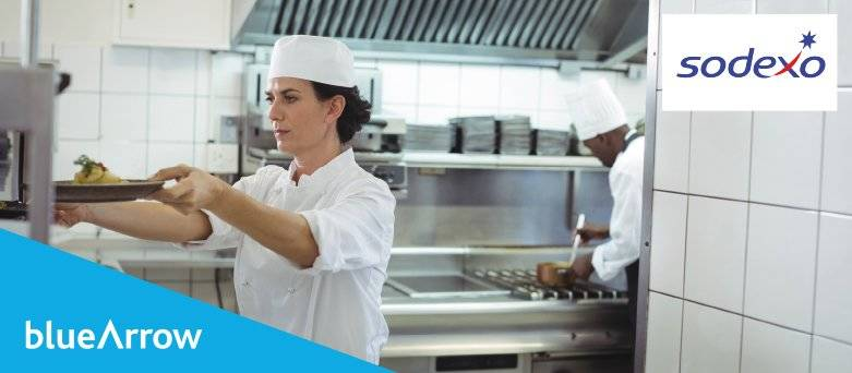Blue Arrow working with Sodexo. Two Chefs in a Kitchen. One Chef preparing food at the cooker. The other Chef putting plates on the serving counter