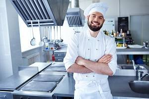 Male chef standing in the kitchen with hands folded