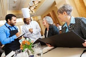 Head chef and waiter talking to 2 females as they order dinner