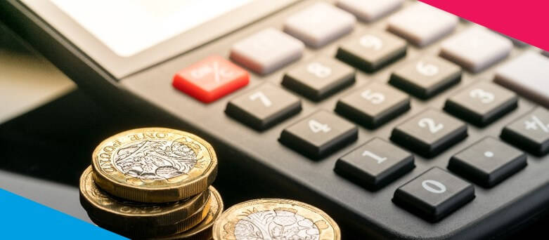Salary Calculator - A Calculator on a desk with pound coins next to it.