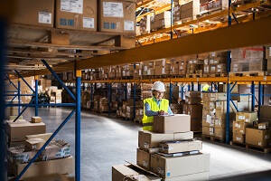 Being a Warehouse Operative  - Female Warehouse Operative leaning on a stack of boxes writing