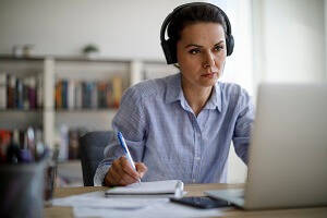 How can I retrain for new UK jobs? Blog image - person on a laptop and headset taking notes in a home office environment